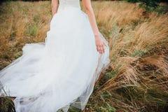 Las manos de la novia hermosa blanda en el primer blanco elegante del vestido de boda Imagenes de archivo