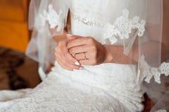 Las manos de la novia hermosa blanda en el vestido de boda blanco elegante Imagenes de archivo
