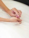 Las manos de la novia que sostienen un collar fotografía de archivo libre de regalías