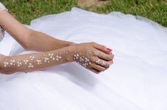 Las manos de la novia se adornan con un modelo de las pequeñas flores blancas en el vestido blanco Fotografía de archivo libre de regalías