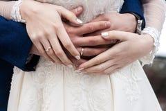 Las manos de la novia y del novio con los anillos se cierran para arriba fotos de archivo