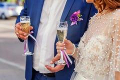 Las manos de la novia y del novio tintinean los vidrios con champán Fotos de archivo
