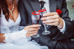 Las manos de la novia y del novio tintinean los vidrios con champán Fotografía de archivo libre de regalías