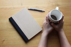Las manos de la señora con la taza, el cuaderno y la pluma del cofee en la tabla Fotos de archivo libres de regalías