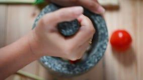 Las manos de la visión superior de la mujer que perforan los chiles y el ajo frescos candentes con la piedra del mortero preparan almacen de metraje de vídeo