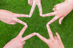 Las manos de las muchachas que hacen la estrella forman sobre hierba Fotos de archivo libres de regalías
