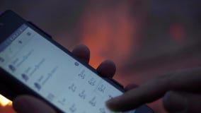 Las manos de las mujeres comunes de las imágenes de vídeo con un smartphone contra la perspectiva del fuego almacen de metraje de vídeo