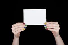 Las manos de las mujeres con los clavos coloreados que sostienen una hoja de papel blanca Fotografía de archivo