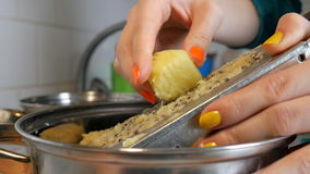 Las manos de las mujeres con un rallador rallan las patatas en la cocina metrajes