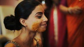 Las manos de las mujeres frotan ligeramente la cara de la novia india cubierta con goma de la cúrcuma almacen de video