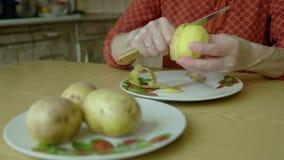 Las manos de las mujeres limpian las patatas metrajes