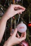 Las manos de las mujeres que adornan el árbol de navidad Imagenes de archivo