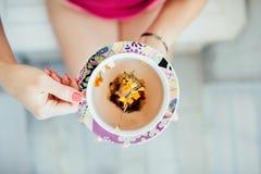 Las manos de las mujeres que sostienen una taza colorida de té Fotos de archivo