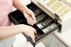 Las manos de los cajeros realizan el cambio Imágenes de archivo libres de regalías