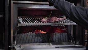 Las manos de los cocineros en guantes negros pusieron el romero encima del pedazo de carne grande en el hueso dentro del horno de almacen de metraje de vídeo
