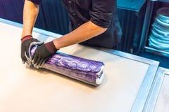 Las manos de los cocineros que ruedan y que mezclan el pequeño azúcar colorido ruedan la internacional Fotos de archivo libres de regalías