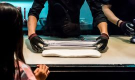 Las manos de los cocineros que ruedan y que mezclan el pequeño azúcar colorido ruedan la internacional Imagen de archivo