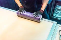 Las manos de los cocineros que ruedan y que mezclan el pequeño azúcar colorido ruedan la internacional Imágenes de archivo libres de regalías