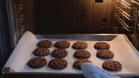 Las manos de los cocineros sacan del horno una bandeja de galletas de harina de avena preparadas almacen de video