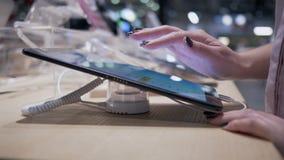 Las manos de los compradores en la tienda de la electrónica eligen un nuevo gadge moderno en el fondo borroso, primer almacen de video