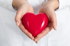 Las manos de los doctores de sexo femenino que llevan a cabo y que cubren el corazón rojo imágenes de archivo libres de regalías