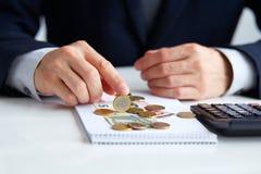 Las manos de los hombres con euros de las monedas Foto de archivo libre de regalías