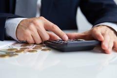 Las manos de los hombres con la calculadora Foto de archivo libre de regalías