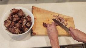 Las manos de los hombres cortaron el filete acabado en pequeños pedazos Asado a la parilla de la carne almacen de video