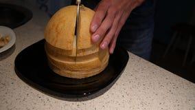 Las manos de los hombres cortaron el primer maduro amarillo del melón Corte el cantalupo en pedazos 4K almacen de video