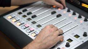 Las manos de los hombres en los apoyabrazos del equalizador ajustan el sonido en el primer del panel del equalizador, radio DJ tr metrajes