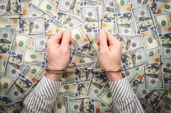 Las manos de los hombres en esposas en el fondo de billetes de dólar imágenes de archivo libres de regalías