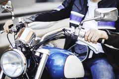 Las manos de los hombres en una motocicleta imagen de archivo libre de regalías