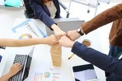 Las manos de los hombres de negocios jovenes que dan el puño topan juntas al tratamiento completo de saludo en oficina Concepto d imágenes de archivo libres de regalías