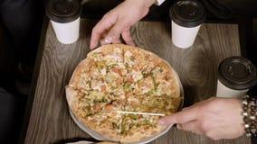 Las manos de los hombres que cortan la pizza con un cuchillo en pedazos Visi?n superior metrajes