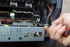 Las manos de los hombres que reparan la impresora laser Fotografía de archivo libre de regalías