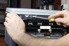Las manos de los hombres que reparan la impresora laser Imagen de archivo
