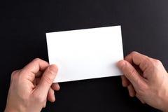 Las manos de los hombres que sostienen una hoja de papel en blanco blanca Imagen de archivo libre de regalías