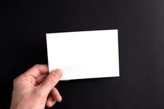 Las manos de los hombres que sostienen una hoja de papel en blanco blanca Imagen de archivo