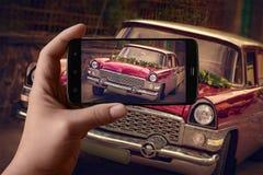 Las manos de los hombres que toman las imágenes del coche en el teléfono Coche festivo del vintage foto de archivo libre de regalías