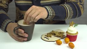 Las manos de los hombres sumergen las galletas del pan de jengibre en cacao En la magdalena y el kumquat de la tabla metrajes