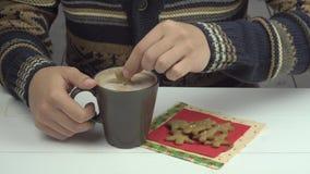Las manos de los hombres sumergieron las galletas del pan de jengibre en cacao almacen de video