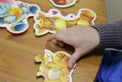 Las manos de los niños apilan rompecabezas del juego fotos de archivo libres de regalías