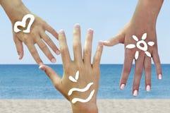 Las manos de los niños con los symbils del mar Foto de archivo