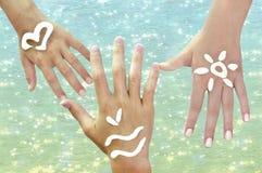 Las manos de los niños con los symbils del mar Imágenes de archivo libres de regalías