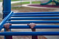 Las manos de los niños en barras de mono foto de archivo
