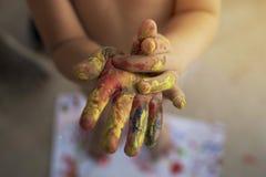 Las manos de los niños en colores foto de archivo