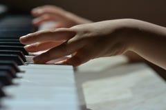 Las manos de los niños en las llaves del piano Imagen de archivo