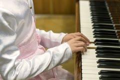 Las manos de los niños en llaves del piano las manos de los niños están jugando el piano foto de archivo