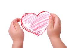 Las manos de los niños están situadas en el gráfico del corazón Imagenes de archivo