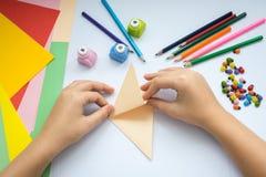 Las manos de los niños hacen el lobo de la papiroflexia del papel del melocotón Foto de archivo